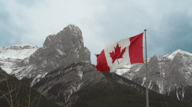 The Canadian flag in front of snow capped mountains.