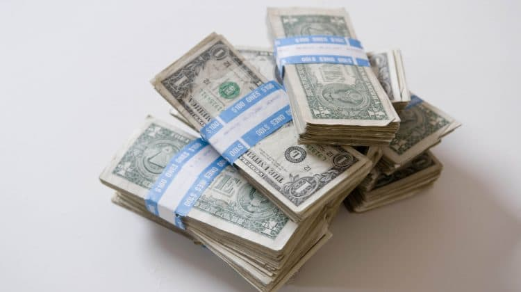 A pile of money representing the cost of geothermal energy.