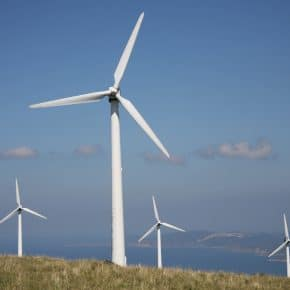 Four wind turbines on top of a hill.