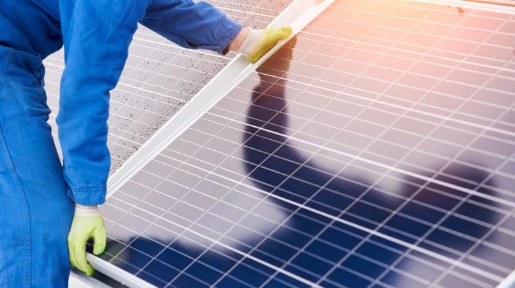 Somebody installing a solar panel.