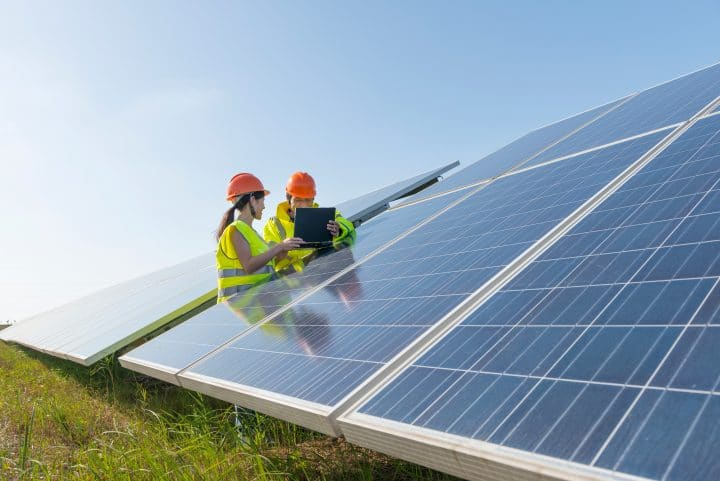 Two renewable energy workers inspecting a solar panel.