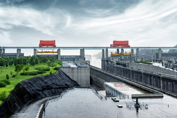 The Three Gorges Dam on the Yangtze River in China surrounded by vegetation.